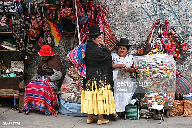 Old women with traditional hats at market stall with souvenirs on display at the witch's market in La Paz Bolivia