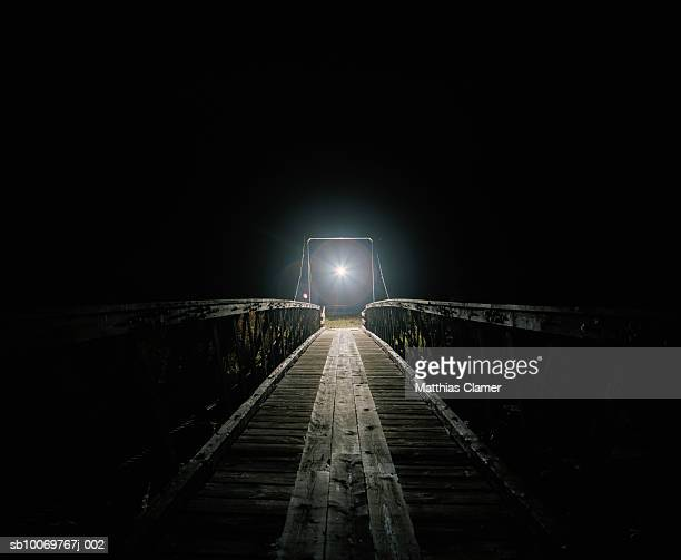 Old wood bridge with mysterious light at night