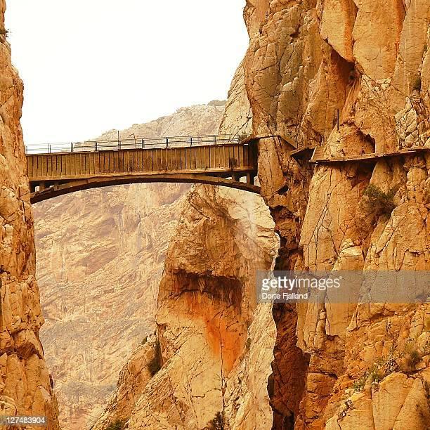 Old wooden bridge between two mountain walls