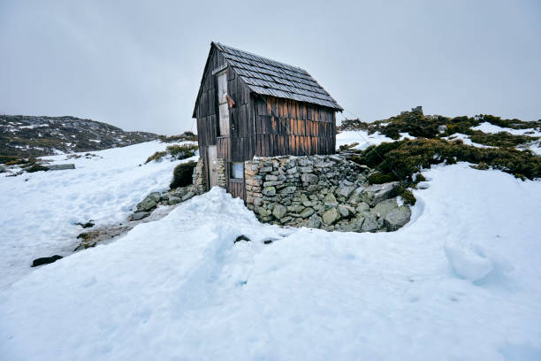 Old wooden cabin, hut in snow, emergency shelter for hikers, Australia