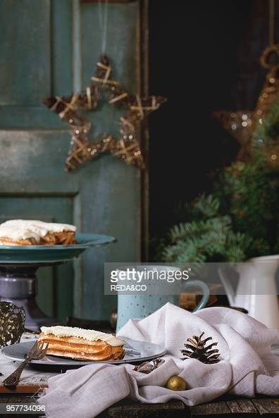 Old Wooden Christmas Table With Butter Cream Eclairs And Mug Of Hot Tea Decorating By Christmas Stars Tree And Vintage Books
