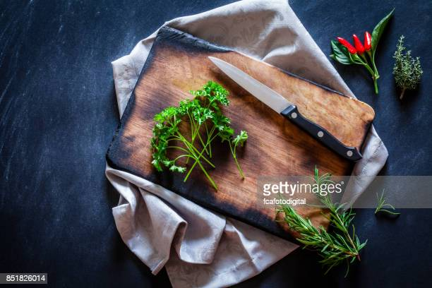 old wooden cutting board with some herbs on dark kitchen table - parsley stock pictures, royalty-free photos & images