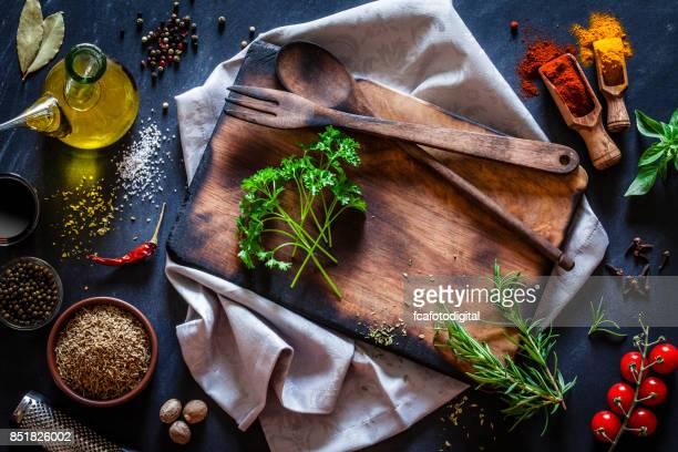 Alten Holzbrett mit Gewürzen und Kräutern auf dunklen Küchentisch
