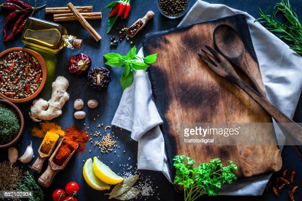 Old wooden cutting board with spices and herbs on dark kitchen table
