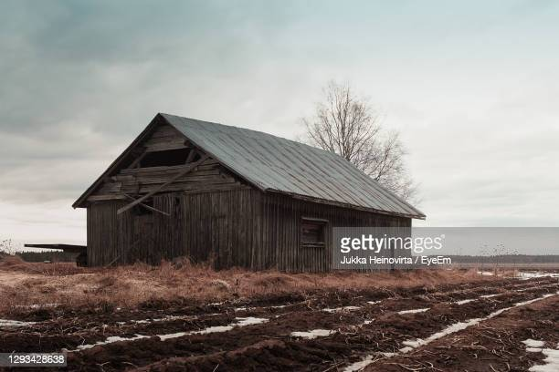 old wooden house on field against sky - heinovirta stock pictures, royalty-free photos & images