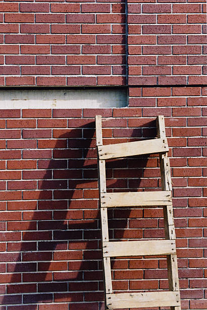Old wooden ladder resting against a brick wall.