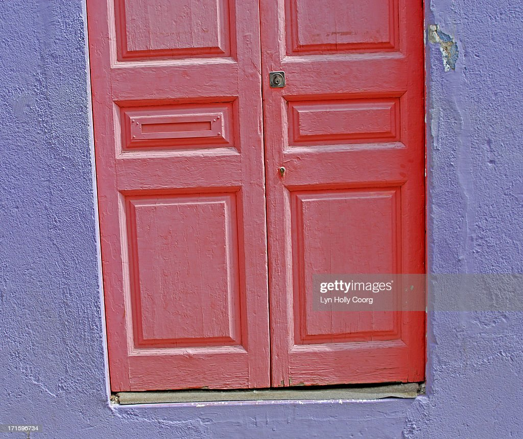 Old wooden red door and purple wall : Stock Photo