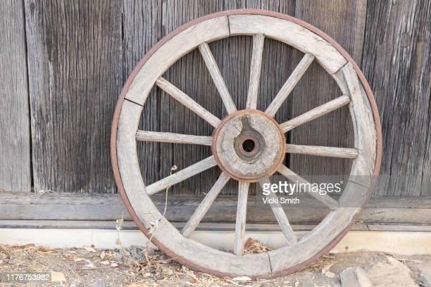 old wooden wagon wheel against a wooden shed - western australia stockfoto's en -beelden