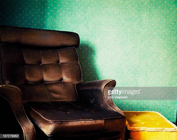 old worn retro armchair, dated home interior - reclining chair stock photos and pictures