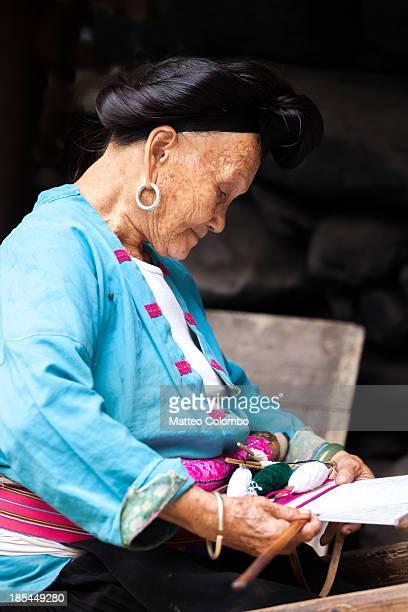 Old Yao minority woman weaving on a wooden loom