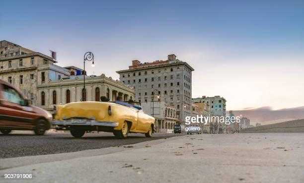 alte gelbe amerikanische Oldtimer am Malecon bei Sonnenuntergang Stunde