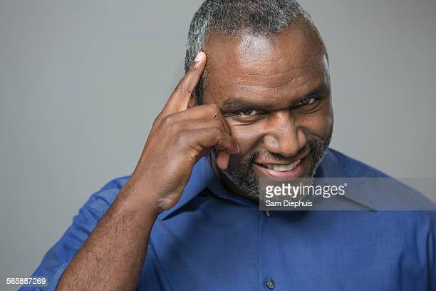 Older African American man tapping his forehead