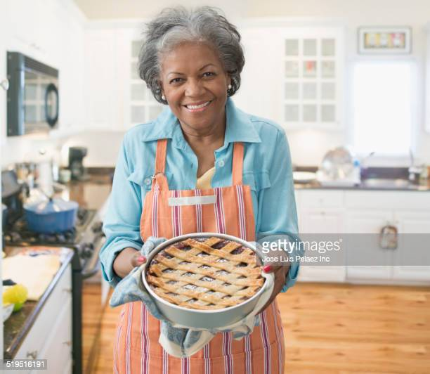 Older African American woman baking pie in kitchen