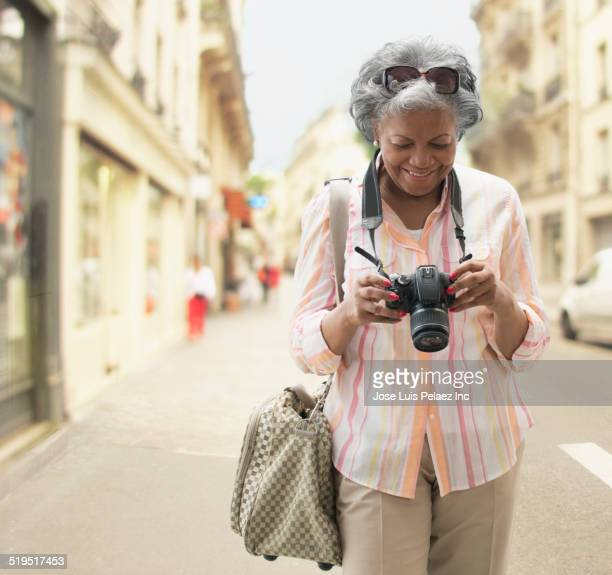 older african american woman checking photographs on digital camera on city street - digital camera stock pictures, royalty-free photos & images