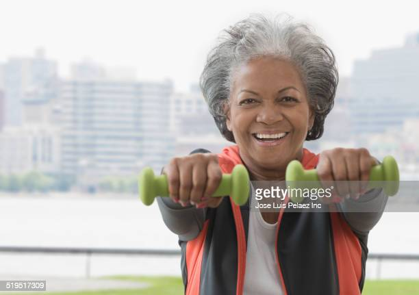 Older African American woman lifting weights at urban waterfront