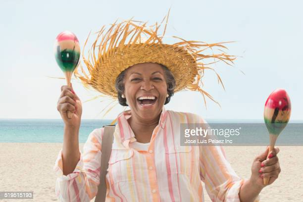 Older African American woman playing maracas on beach