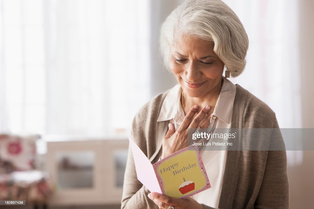 Older African American woman reading birthday card : Stock Photo