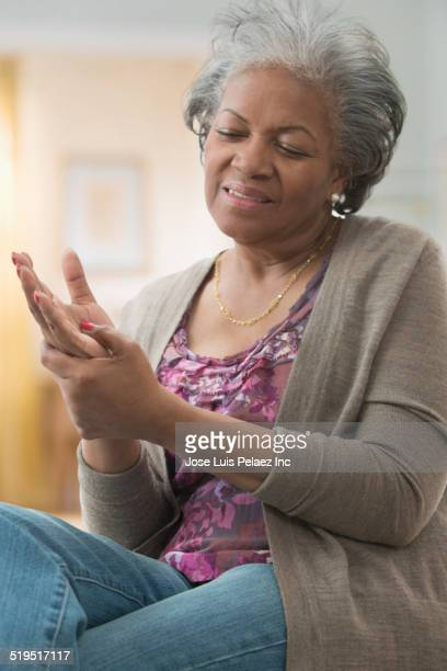 older african american woman rubbing her hand - massage black woman stock photos and pictures