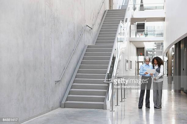 older and young woman looking at papers - staircase stock-fotos und bilder