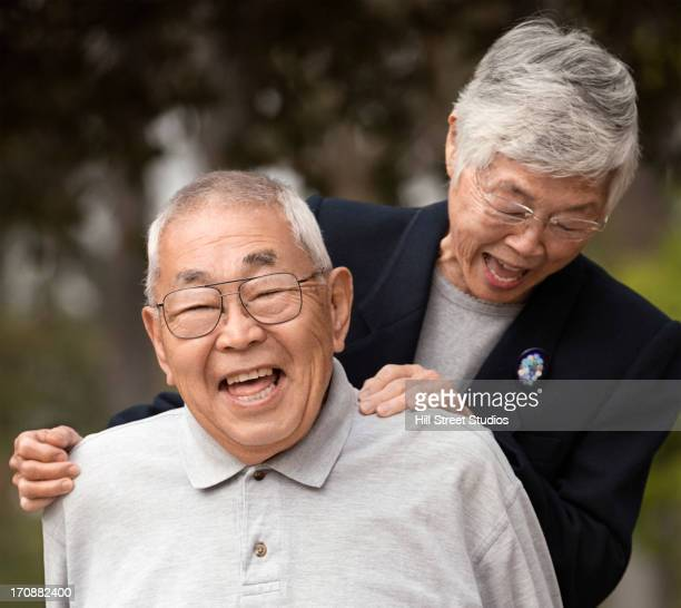 older asian couple laughing together outdoors - korean ethnicity stock pictures, royalty-free photos & images