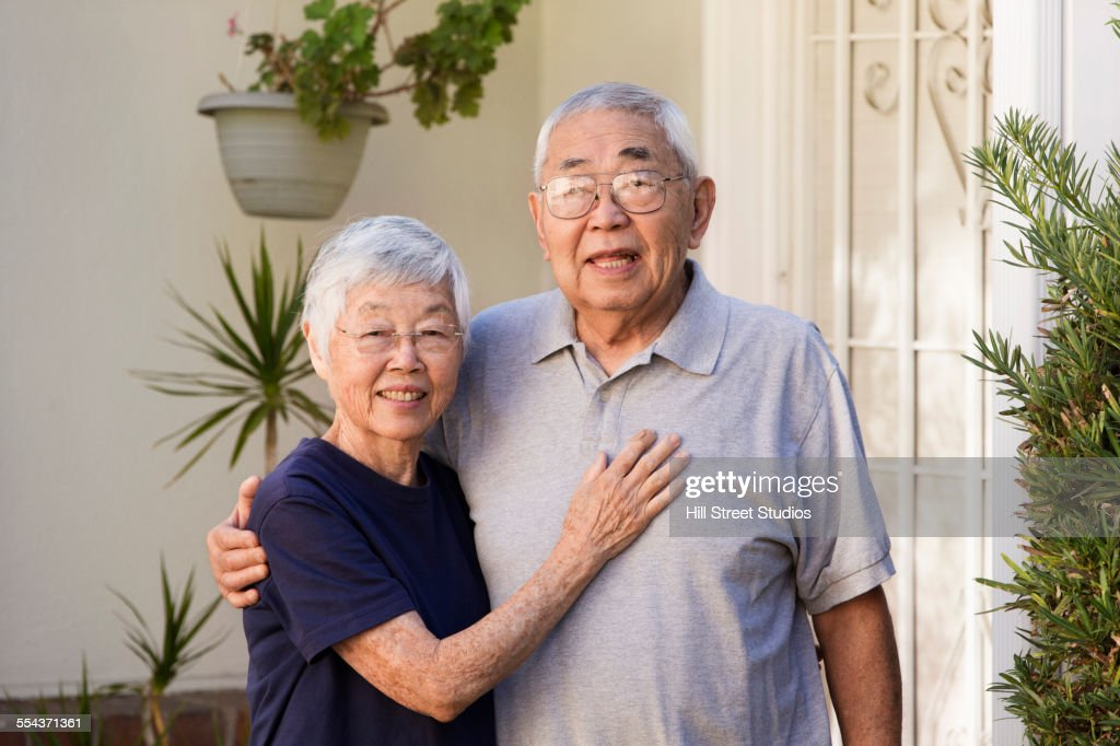 Older Asian couple smiling outdoors : Foto de stock
