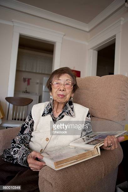 Older Asian woman looking at photo album