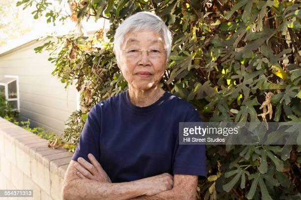 Older Asian woman standing in garden