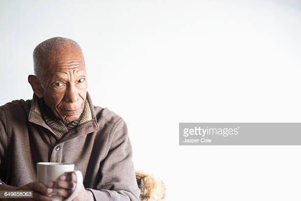 Older Black man drinking cup of coffee