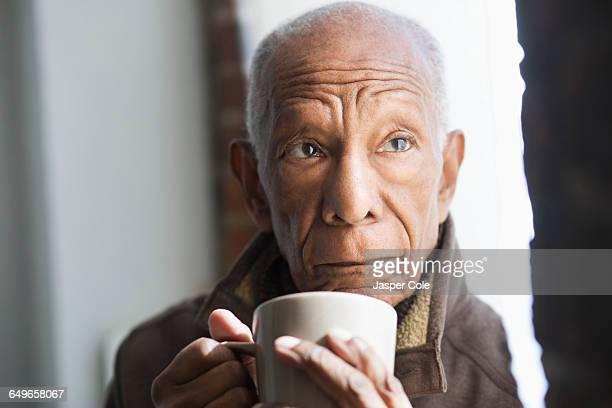 Older Black man drinking cup of coffee