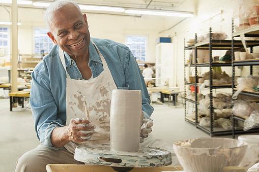 Older black man forming pottery on wheel in studio - gettyimageskorea