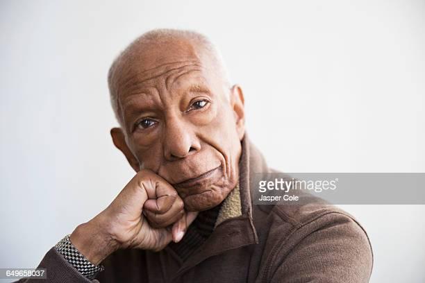 older black man resting chin in hand - kin in de hand stockfoto's en -beelden