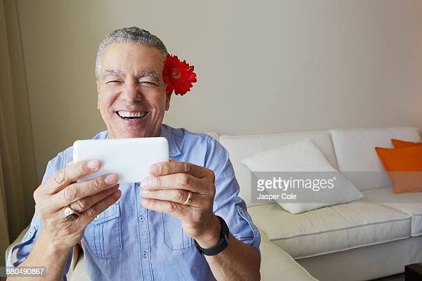 Older Black man taking selfie with flower behind his ear