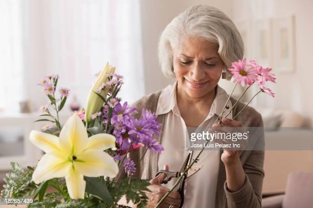 Older Black woman arranging flowers