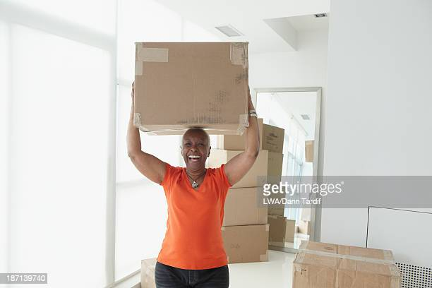 older black woman carrying box in new home - medium group of objects stock pictures, royalty-free photos & images