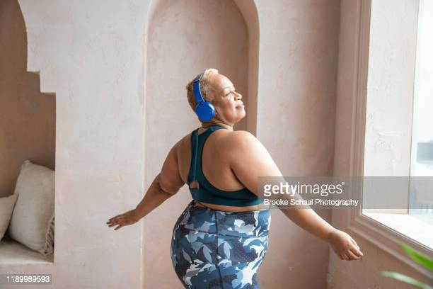 older black woman dancing with headphones on - femme pulpeuse photos et images de collection