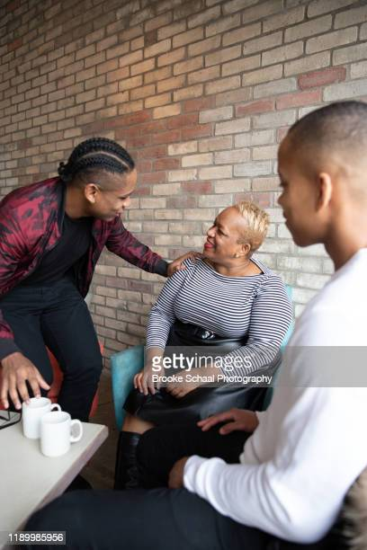older black woman in a cafe having coffee with her sons - ambassador stock pictures, royalty-free photos & images
