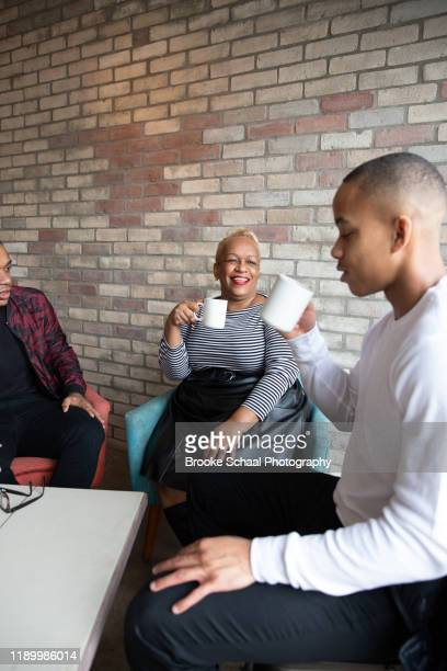 older black woman in a cafe having coffee with her sons - chesty love stock pictures, royalty-free photos & images