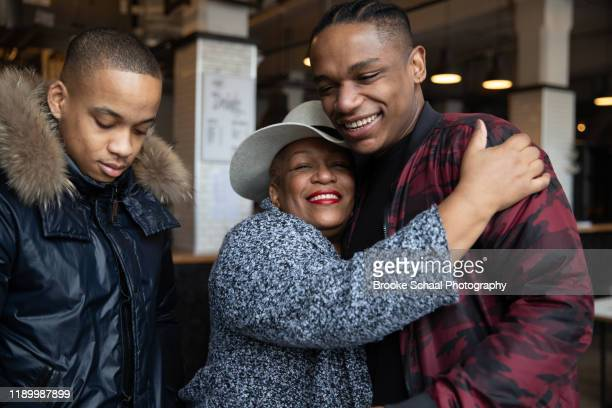 older black woman in a cafe having coffee with her sons - showus stock pictures, royalty-free photos & images