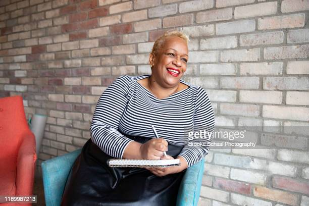 older black woman in a cafe - showus stock pictures, royalty-free photos & images
