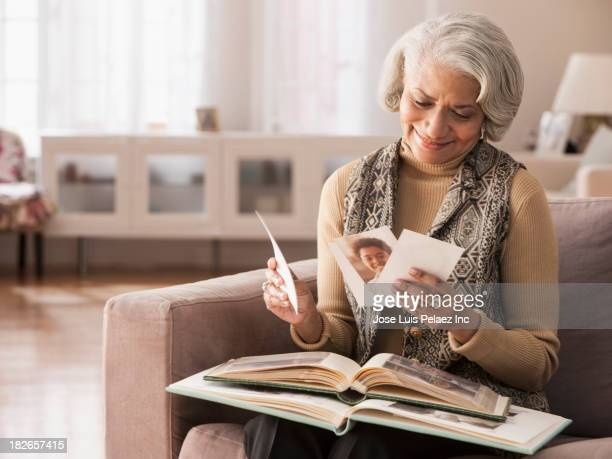 older black woman looking at photographs - nostalgia stock pictures, royalty-free photos & images