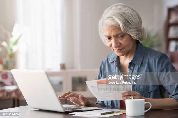 Older Black woman paying bills on laptop