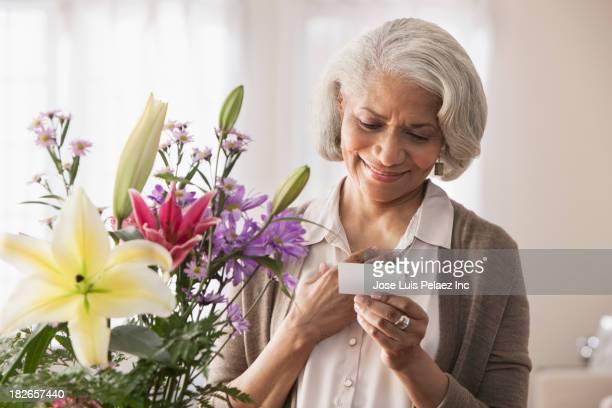 Older Black woman receiving bouquet of flowers