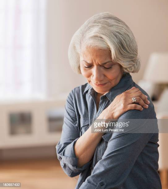 older black woman rubbing her shoulder - shoulder stock pictures, royalty-free photos & images