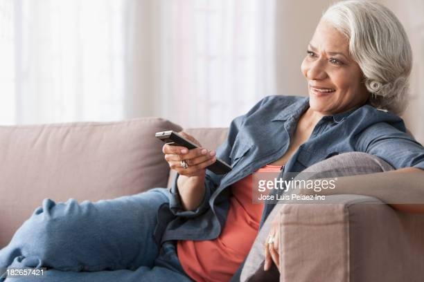 Older Black woman watching television on sofa