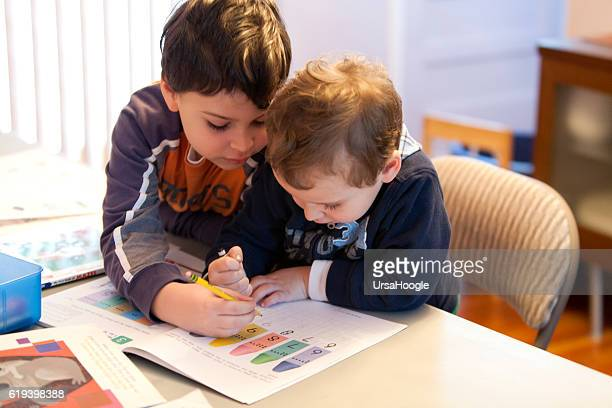 Older brother helps younger brother with schoolwork at home