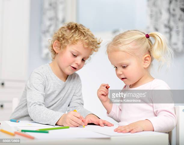 Older brother teaches his younger sister to crayon