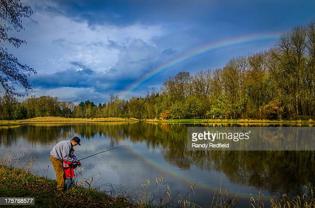 Older brother teaches younger to fish at Trojan pond in Prescott Oregon. A beautiful sky with a colorful rainbow is casting its reflection in the...