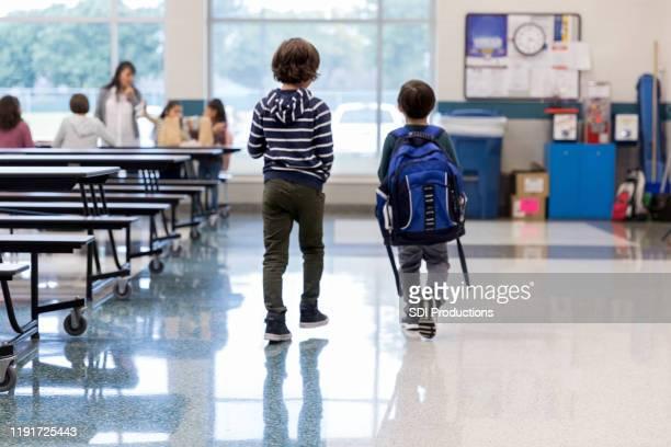 älterer bruder geht kleinen bruder zum mittagessen in cafeteria - staatliche schule stock-fotos und bilder