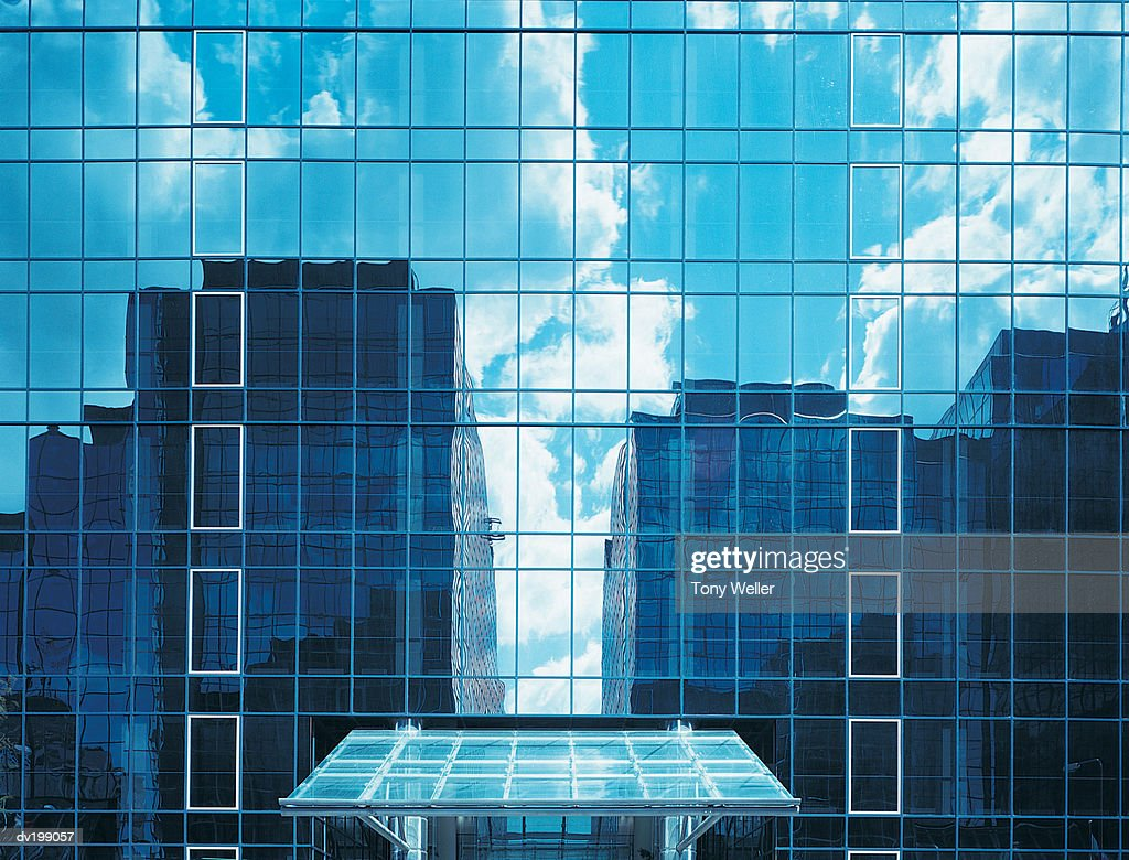 Older buildings reflected in mirrored-like windows : Stock Photo