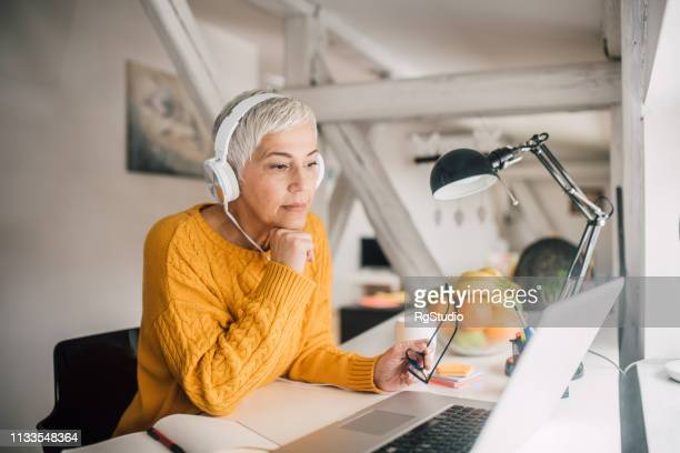older business woman with headphones - online class stock pictures, royalty-free photos & images